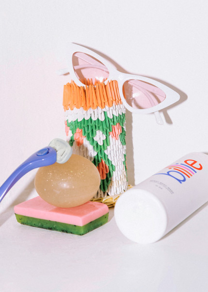 Periwinkle handle leaning on soap in front of a knitted phone case with a pair of sunglasses on top next to a bottle of Body Wash laying on its side