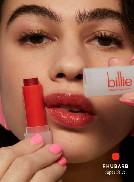 model holding a Rhubarb Super Salve next to their Rhubarb tinted lips